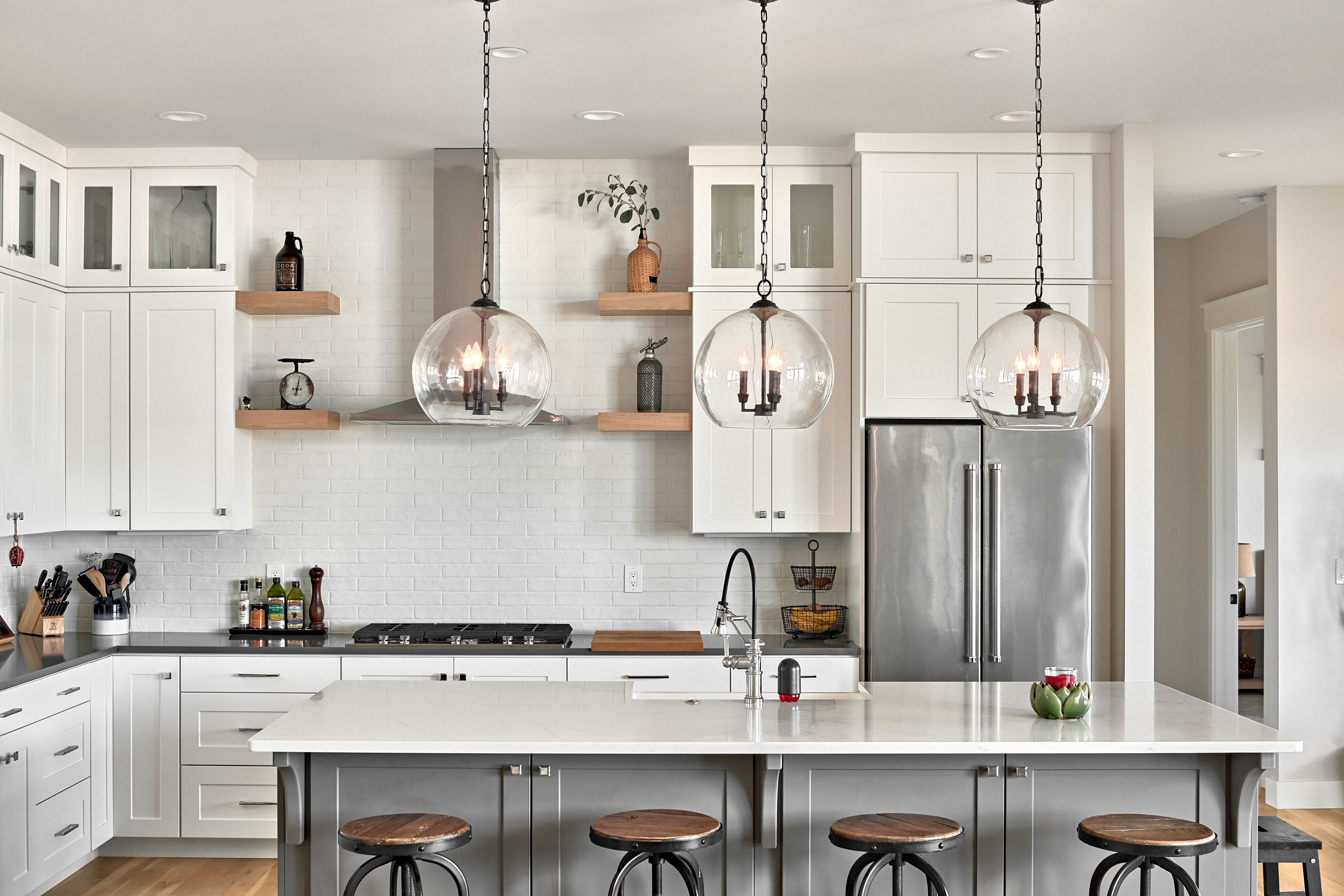 Interior photography of kitchen with glass globe pendants–Timnath, Colorado residence located in Wild Wing.